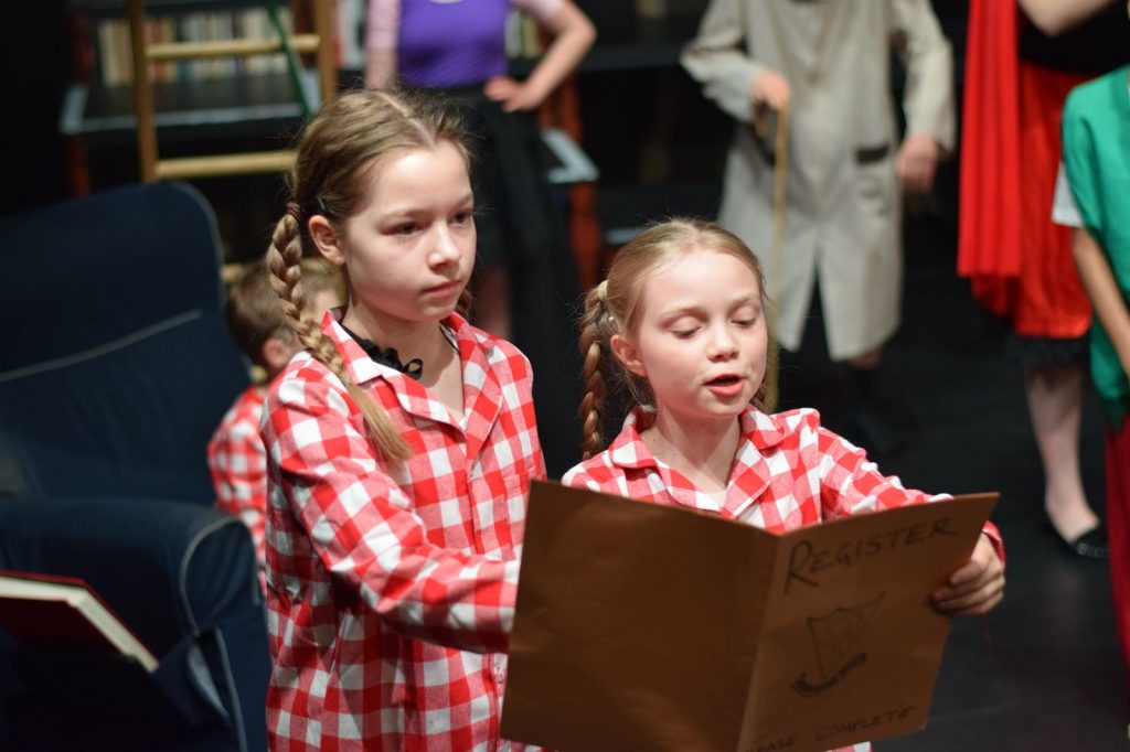 Two young girls on stage one reading from a book