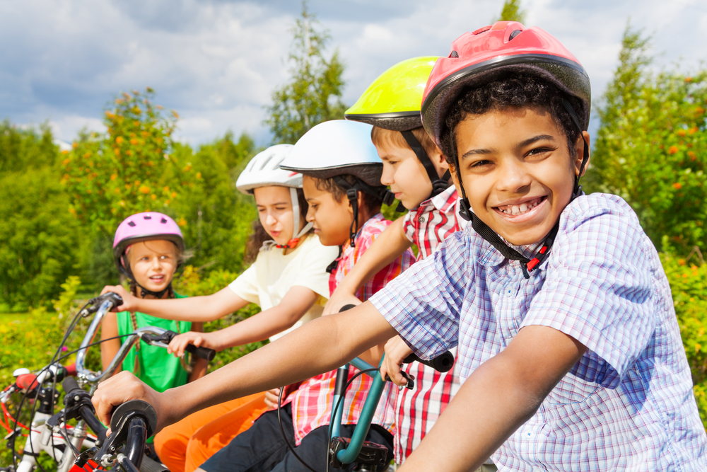 children on bikes wearing helmets and smiling