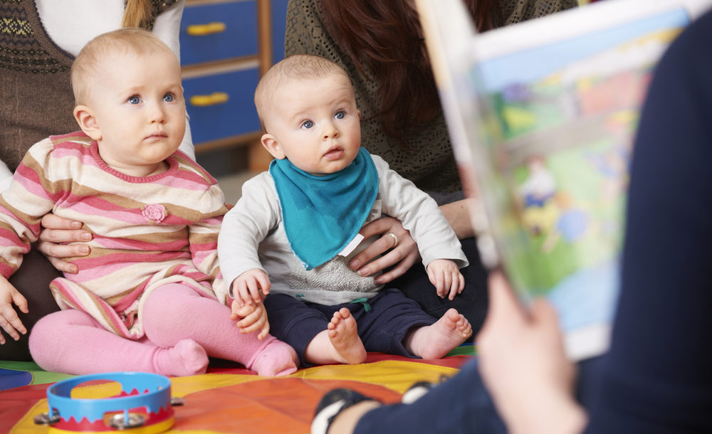 woman reading a story to babies in library
