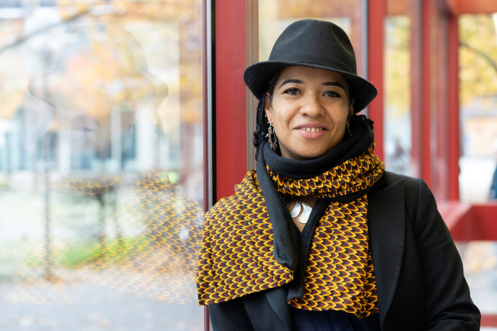 woman wearing hat and scarf smiling at camera