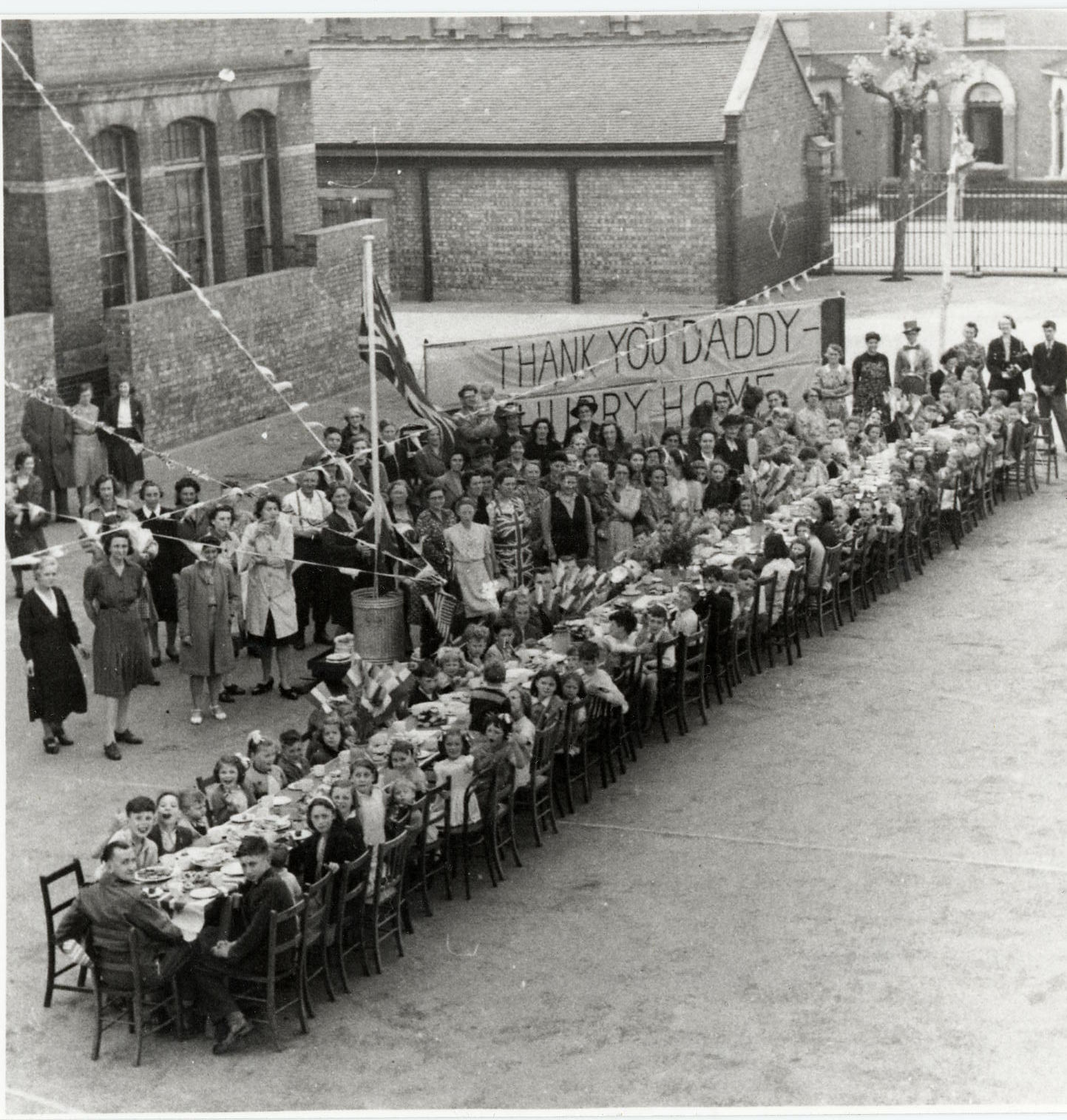 Families sitting at tables outside during welcome home party for their fathers after the Second World War